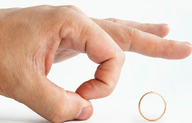 Close up of person's hand pushing away wedding golden ring isolated on white. Man makes finger kick of a ring. Male unwilligness to stay married. Disillusionment in marriage. Divorce initiated by men